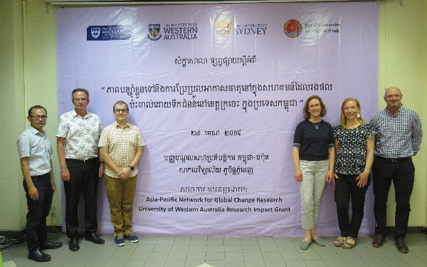 Members of the research team pose in front of the workshop banner